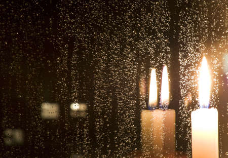 downpour: Rain drops reflect light of a burning candle in glass at night