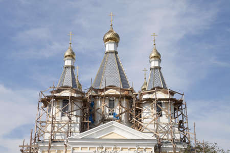 adaptations: Domes of a cathedral against the blue sky with adaptations for repair