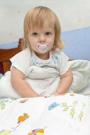 The small child with a dummy sits on a bed under a blanket, only having woken up Фото со стока