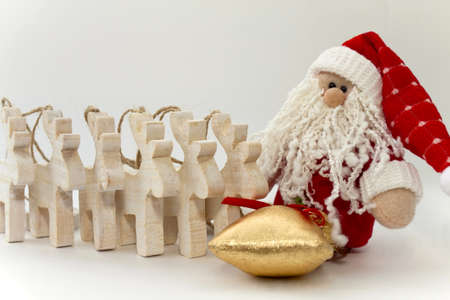 Toy Santa Claus with gifts and reindeers on the white photo