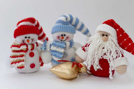 Rag snowmen and Santa Claus with a bag of gifts on the white photo