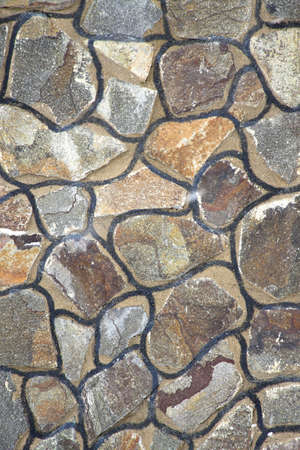creative potential: Wall from multi-coloured stones of the various form fastened by clay Stock Photo