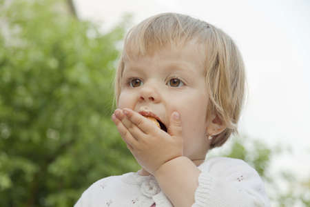pushes: The small child pushes a pie piece in a mouth Stock Photo