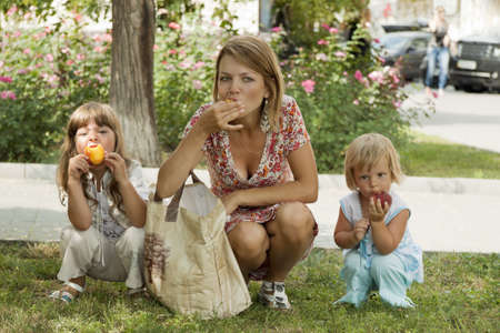 Mum with daughters have sat down in a tree shade to eat peaches photo