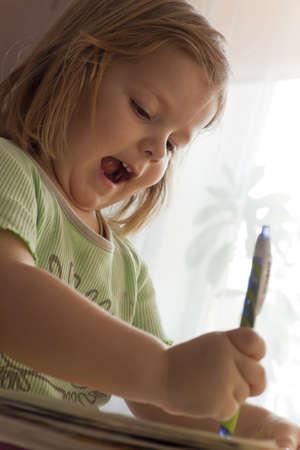child with enthusiasm write opposite to a window photo