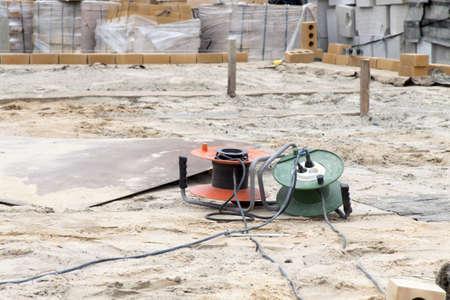 unwound: unwound extension pieces lie on sand among bricks and blocks