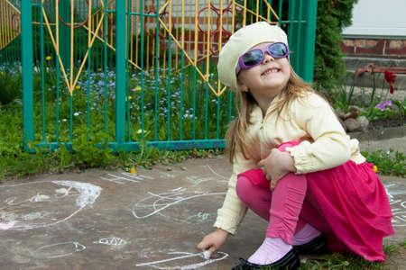 joyful girl draws on a path