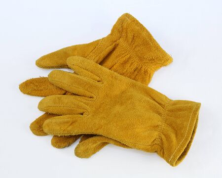 Worn, suede leather work gloves isolated on a white background photo