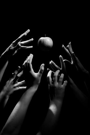 Hands reach for an apple