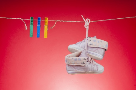 Childrens shoes are drying on a rope