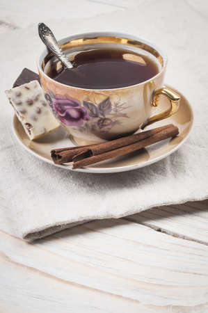 Ð¡up of tea with cinnamon and sweets photo