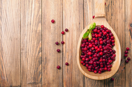 cranberries in wooden spoon on table Stock Photo