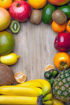 Composition of tropical fruits in the form of a frame on a wooden board photo