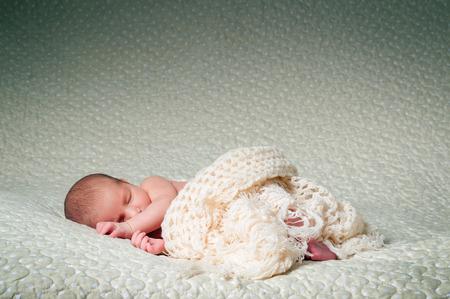 pasgeboren baby slapen op een grote crème sprei
