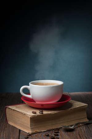 hete koffie op het oude boek op donkere achtergrond