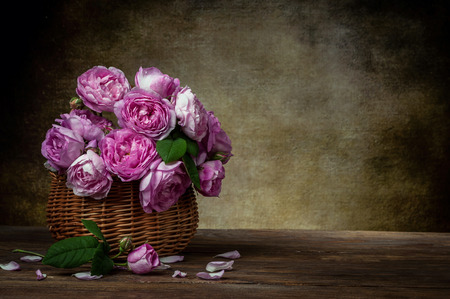 tea rose in basket on old retro background