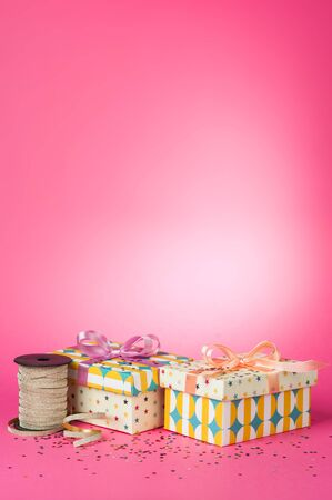 Colorful gift boxes with bow and ribbon on a pink background