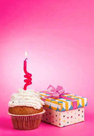 cupcake with candle and  gift on pink background