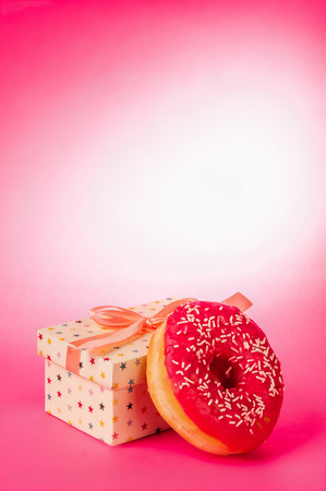 donut and gift on a pink background