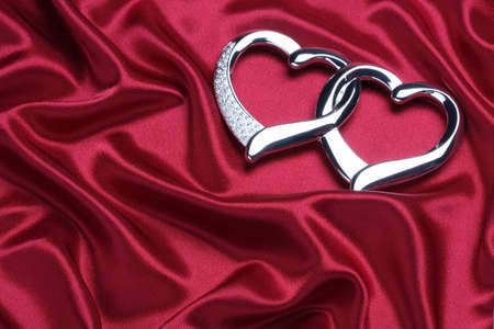 red smooth and elegant satin with hearts Stock Photo