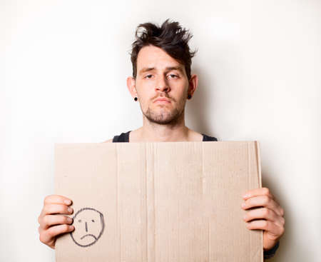 Homeless man holding blank cardboard sign Stock Photo