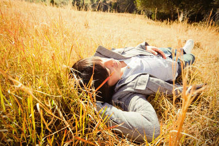 Young man rest on golden field. Stock Photo