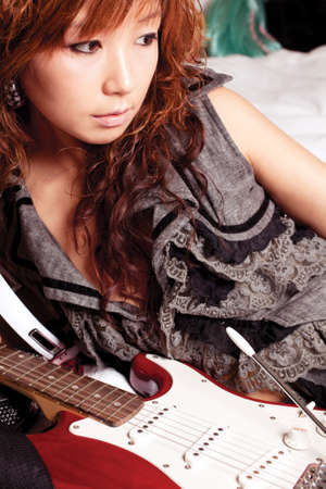 Young asian woman with a red guitar.