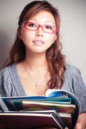 Asian girl holding a textbook. Wear glasses.