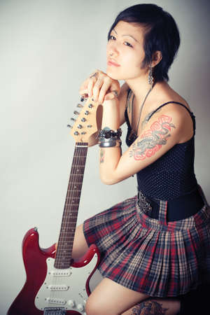 Funky young woman with her red hot guitar.