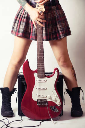 Funky young woman with her red hot guitar. photo