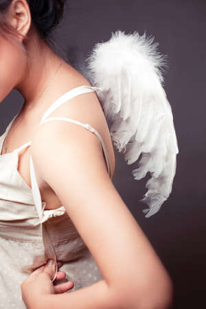 Girl wearing a white top with wings. Stock Photo