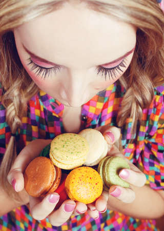 A young woman loves her sweet macaron. photo