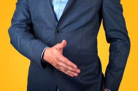 extending: businessman extending hand to shake isolated