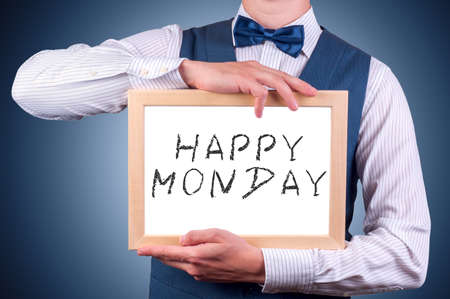 mondays: a man with a sign in his hands with the words happy mondays Stock Photo