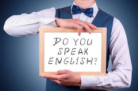 linguistics: man with a sign in his hand with the question do you speak english
