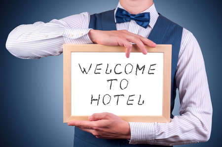 a man with a sign in his hand with the inscription welcome to the hotel