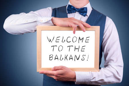 balkans: a man with a sign in his hand with the inscription welcome to the Balkans Stock Photo