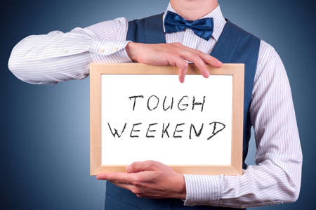 tough: a man with a sign in his hands with an inscription tough weekend Stock Photo