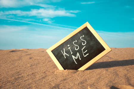 closeup of a chalkboard with a wooden frame and the word kiss me written in it, placed on the sand of a beach
