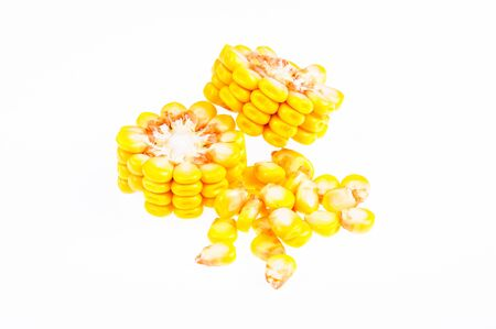 Ripe corn on the cob divided into pieces on a white background