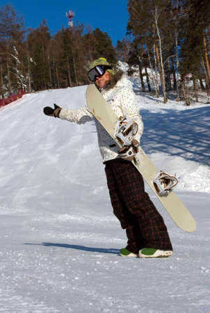 A young woman holding a snowboard on the slope photo
