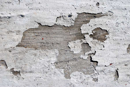 A closeup view of the texture and look of white paint cracking and peeling from a concrete wall.