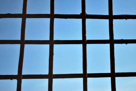 Grid of steel bars with blue sky background. Stock Photo