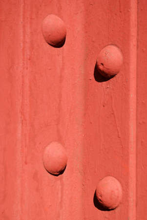 bolted: A closeup, detailed view of two steel girders, bolted together and painted red.
