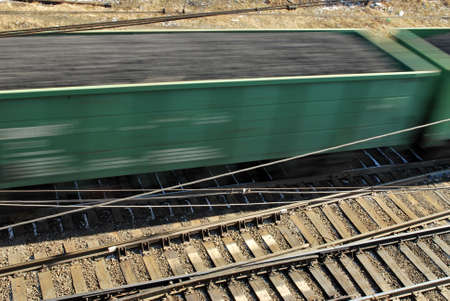High perspective closeup of a moving freight train and tracks. Motion blur.