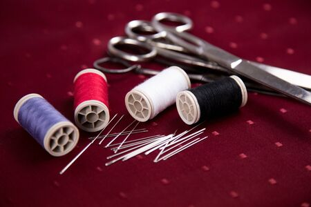 thread reel needle red background
