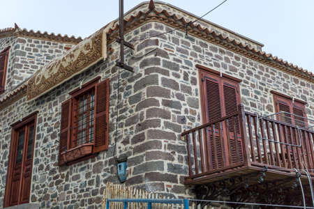 Old stone building with a carpet on its roof in a greek island