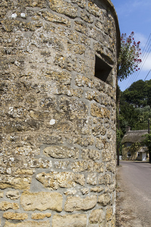 loophole: A wall with a loophole cut into it for World War Two anti invasion defence. This at the gate to the church in Loders, Dorset, England, United Kingdom.