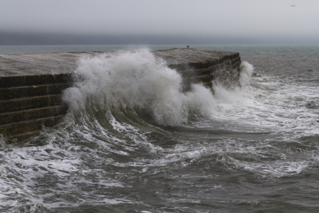 Waves crashing over The Cobb – which protects the harbour. Famous scene in the film 'The French Lieutenant's Woman' with Meryl Streep. Stock Photo - 23388329