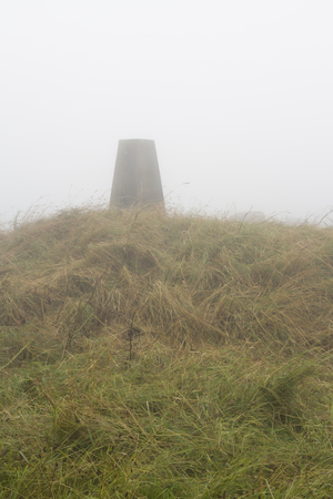 triangulation: In low lying cloud, triangulation Point on Eggardon Hill, Dorset, England, United Kingdom. Stock Photo